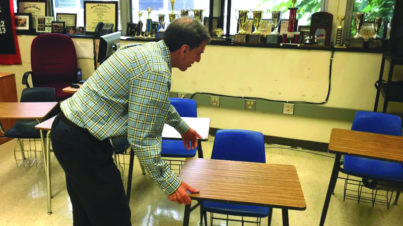 """Theory of Knowledge teacher Mr. Scharff moves desks to accommodate the next class. Mr. Scharff has had to move the desks at the end of every block 3 class because of the difference in size between his classes. """"One difficulty is that theory of knowledge was designed to be a seminar and having class discussions becomes difficult,"""" said Mr. Scharff. (Photo: Dorian Charpentier)"""
