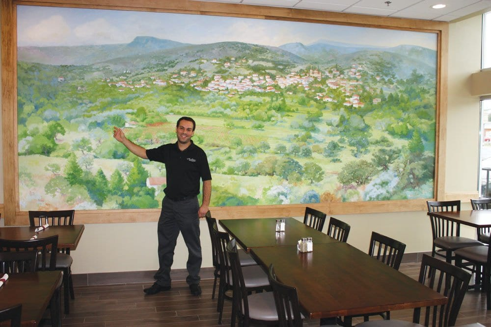peter zoutis, GENERAL MANAGER of ANTHONY'S and son-in-law of owners Tony and Faye Yianiarrakis points to the home he grew up in, visible in a mural at the restaurant painted by Alexia Scott depicting the village of Niata in southern Greece, where both Faye and Peter are from.  (Photo: News-Press)