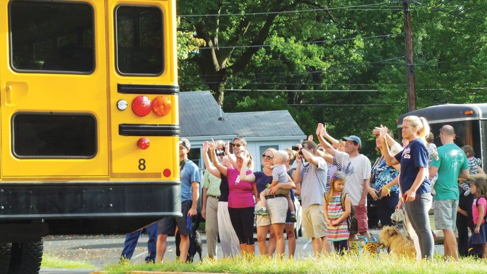 PARENTS WAVE GOODBYE to children embarking upon their first day back to school at Falls Church City Schools Tuesday. Initial reports showed lower-than-expected enrollment after the first day.  (Photo: John Wesley Brett/FCCPS)