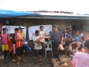 (center, stripe shirt) Arman Mulleem of Worldwide Filipino Alliance distributing relief goods