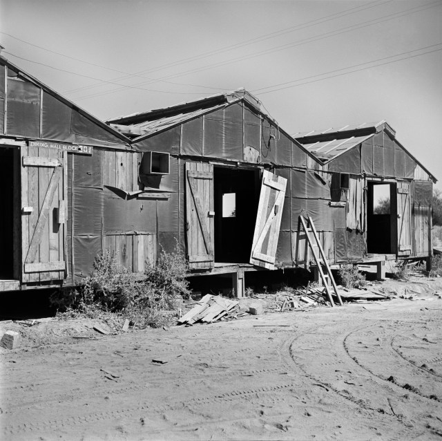 """Decaying barracks at the Poston Relocation Center in Arizona several months after the departure of the """"evacuees."""" Hikaru Iwasaki 1945"""