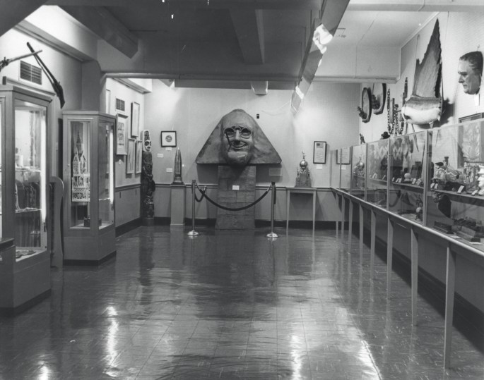 Black and white photo of an exhibit hall with glass cases on the sides filled with artifacts and a sculpture of FDR as the sphinx in the middle
