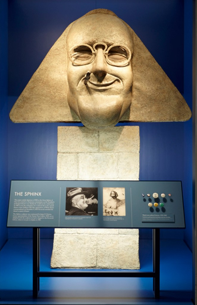 Sculpture of FDR as the Sphinx with glasses and a cigarette, behind glass with exhibit text panel and colorful buttons below