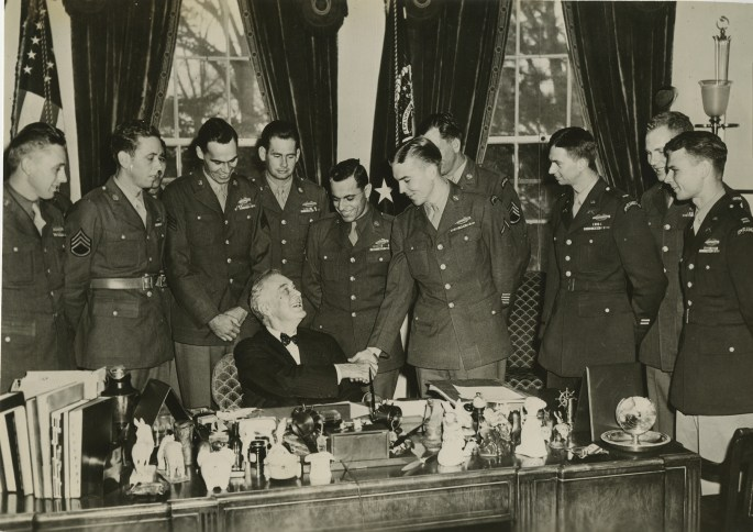 FDR sitting at his desk and shaking hands with one of the many men in uniform behind him