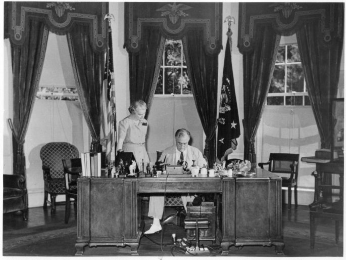 Black and white image of FDR sitting at his desk with Marguerite LeHand standing next to him