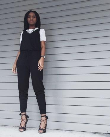 white t-shirt, black jumpsuit, diamond necklace, black watch, black lace up heels