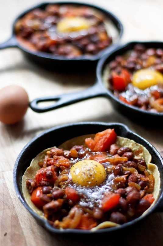 Huevos Rancheros Skillet Eggs- with hearty beans, crispy tortilla, avocado and fresh tomato and cilantro...so simple and tasty! | www.feastingathome.com