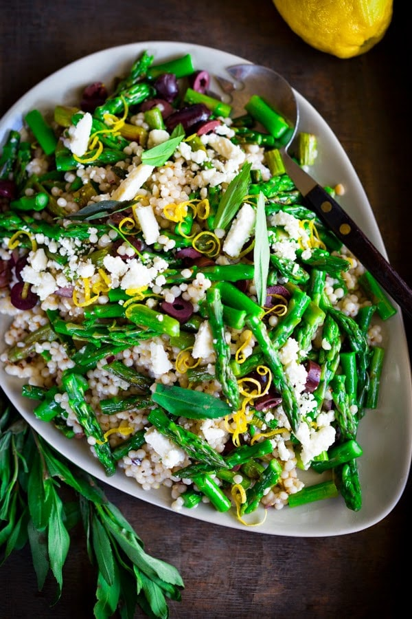 A delicious recipe for Spring Asparagus Salad with Cous Cous, kalamata olives, lemon zest and Mint in a zesty lemony dressing.| www.feastingathome.com