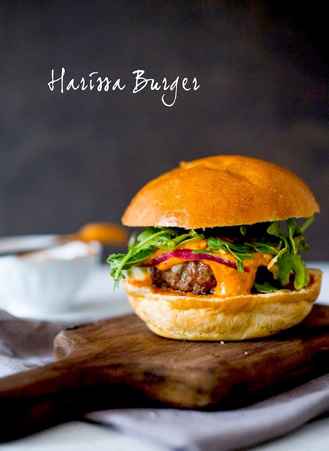 Grilled juicy Harissa Burger with harissa aioli, arugula, pickled onions on Brioche Bun | www.feastingathome.com