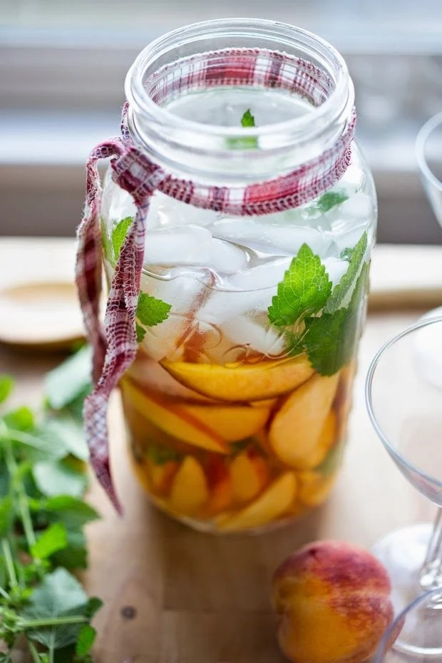 A simple recipe for Peach Sangria ...a refreshing summer drink with wine and Elder flower liquor ( or syrup)  that can be made ahead. Delicious! | www.feastingathome.com