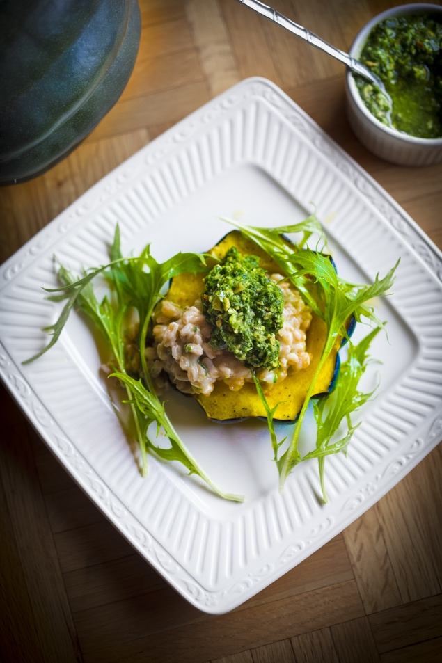 A delicious fall recipe - Roasted Acorn Squash w/ Farro Risotto and Radish Top Pesto- a perfect vegetarian main course,  created by chef Tony Brown of Ruins.  | www.feastingathome.com