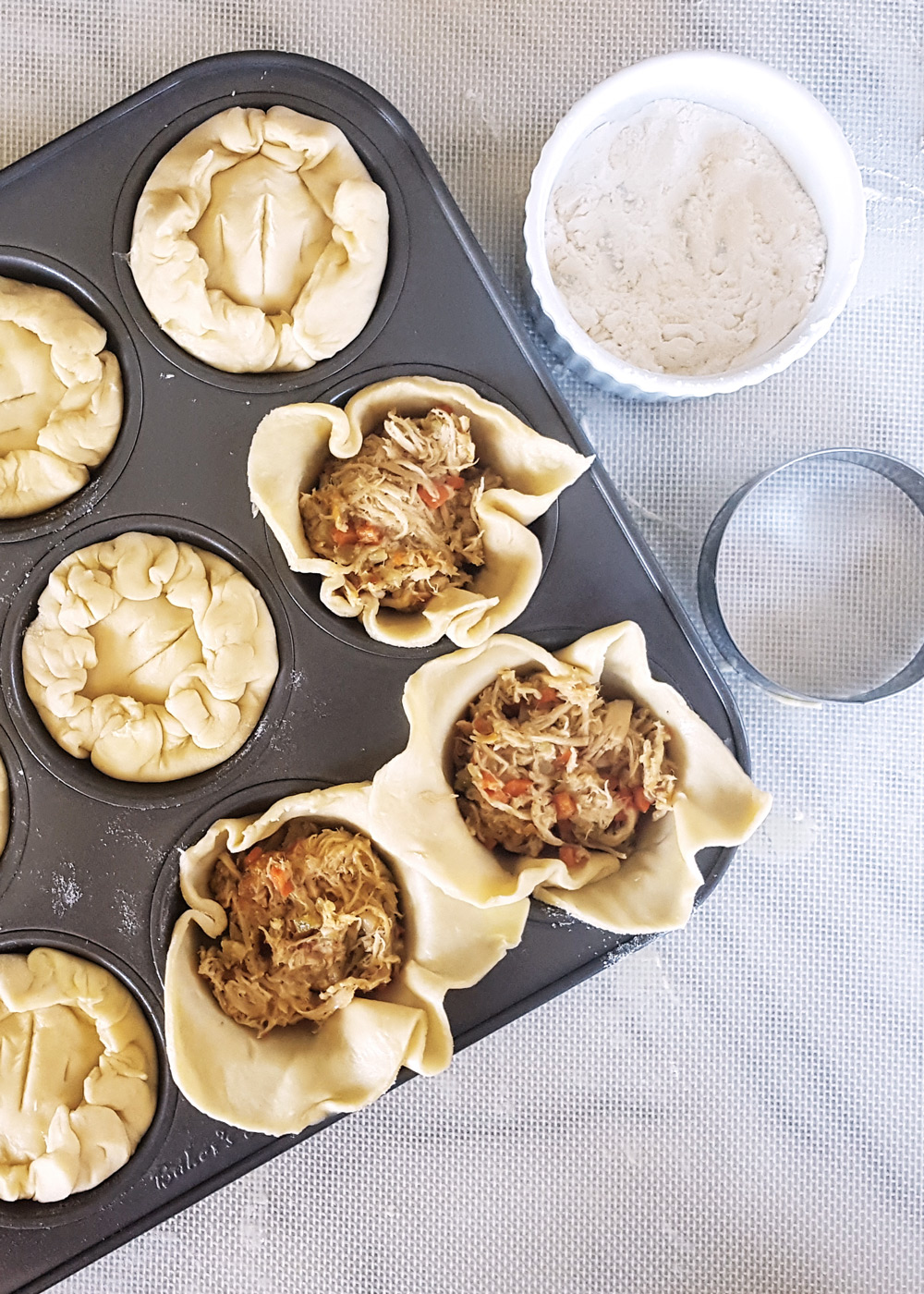 Assembling mini pies. | Mini Apricot Rosemary Chicken Pies | FeastInThyme.com