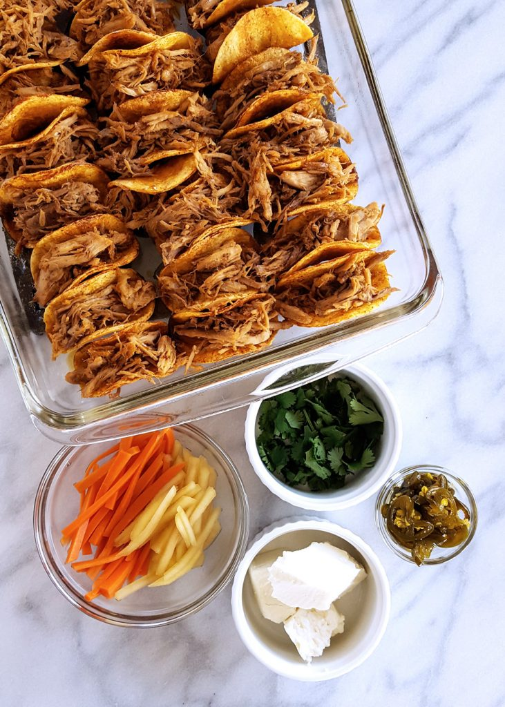 Pulled Pork Mini Tacos lined in a baking tray, drizzled with Spicy Sweet Soy Glaze with garnish on the side. #SuperBowl #Party #TinyFood #Tacos | FeastInThyme.com