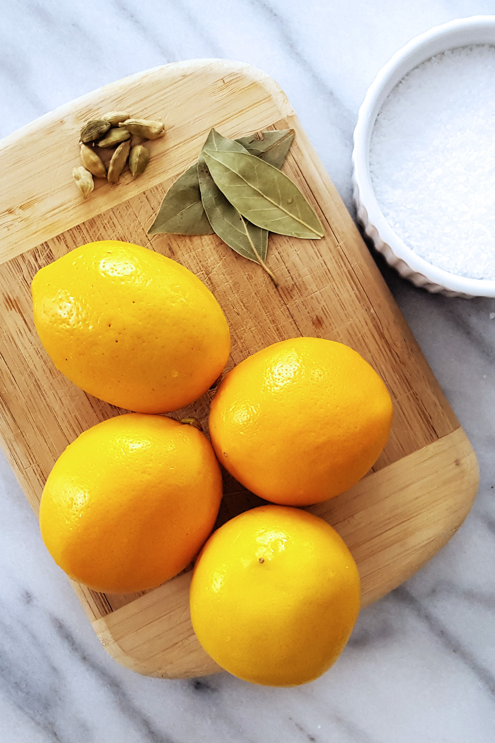 Small Batch Preserved Lemons with Bay Leaves & Cardamom add some sunny brightness to your meals all year long. #lemons #preserving #homemade | FeastInThyme.com