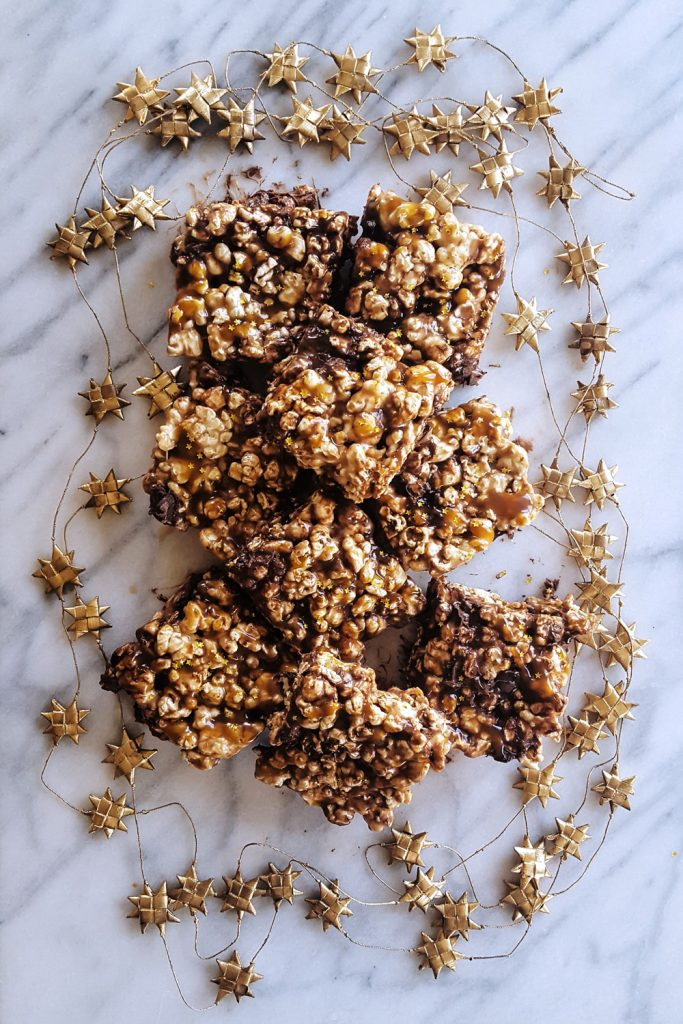 Pile of Salted Caramel Popcorn Bars surrounded by gold stars. | FeastInThyme.com