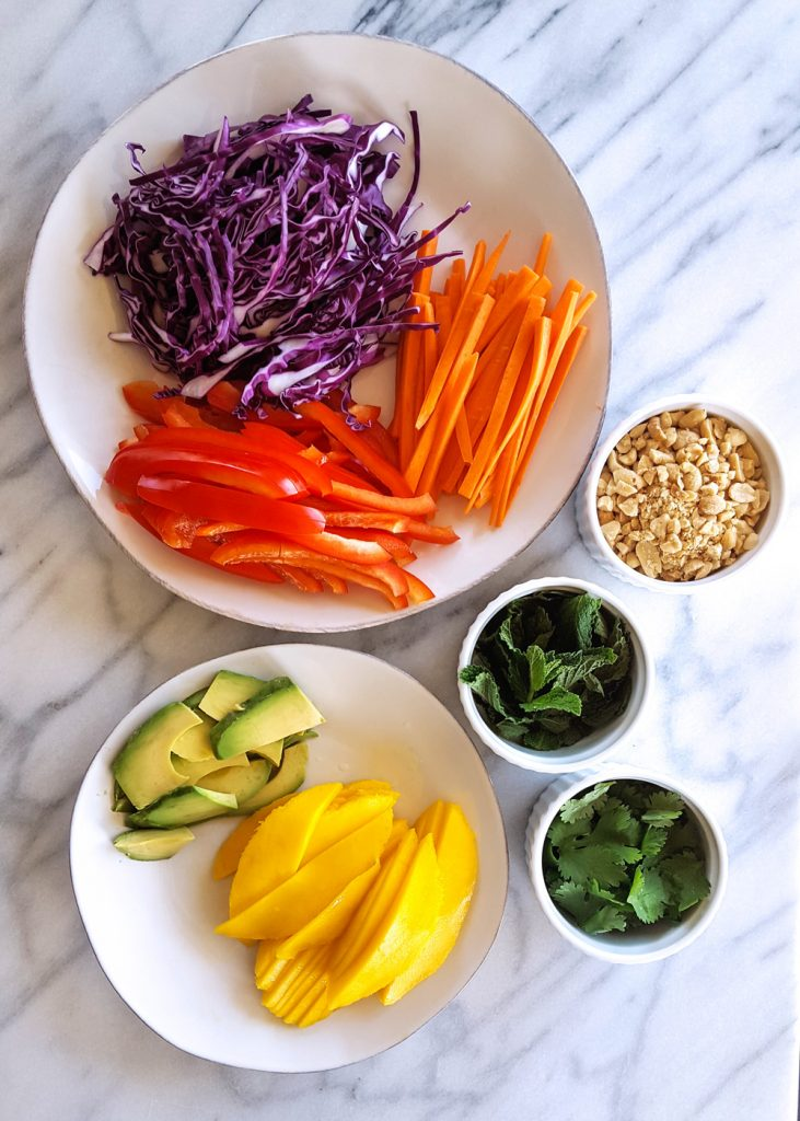 Assembly line of prepped vegetables, mango, and herbs. | Sesame Lime Roasted Shrimp Summer Rolls