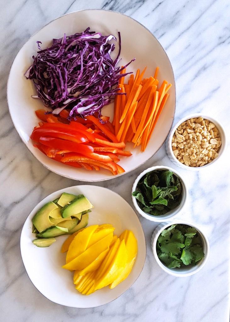 Assembly line of prepped vegetables, mango, and herbs. | Sesame Lime Roasted Shrimp Summer Rolls