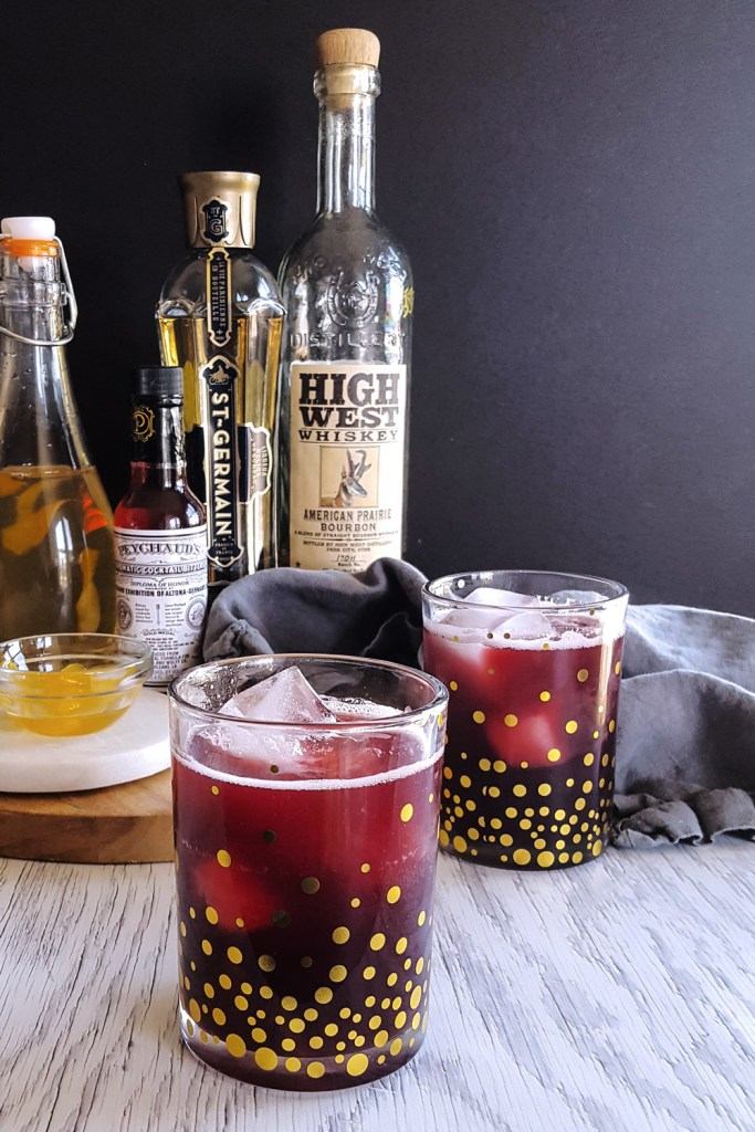 Two rocks glasses of vibrant red pomegranate bourbon cocktail against a black background.