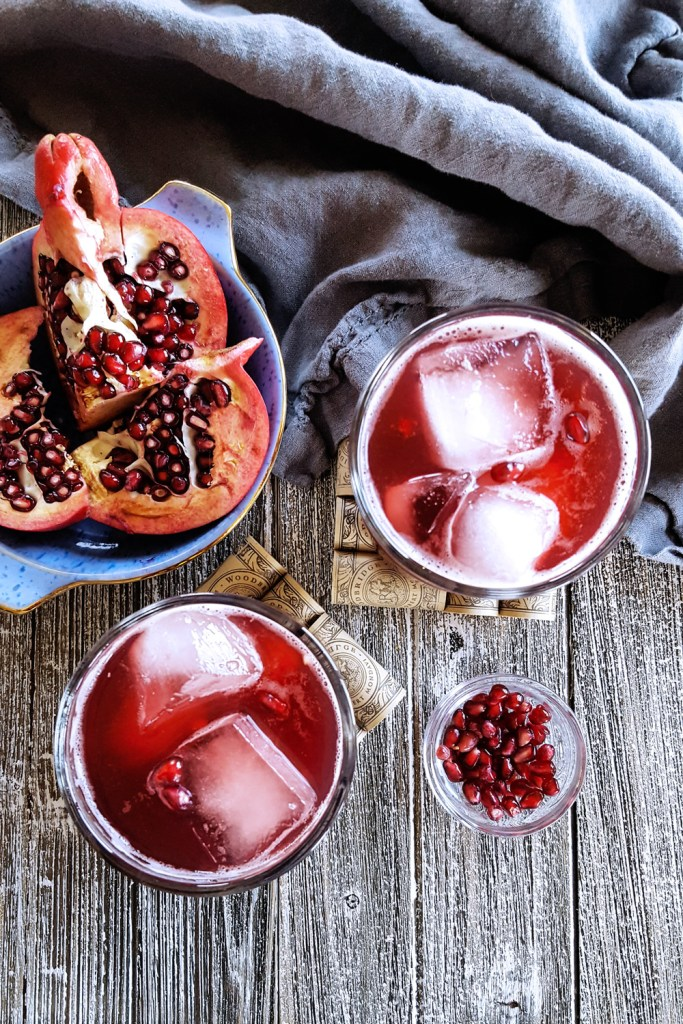 Two glasses of pomegranate bourbon cocktail on wooden blanks, with a bowl of pomegranate arils.