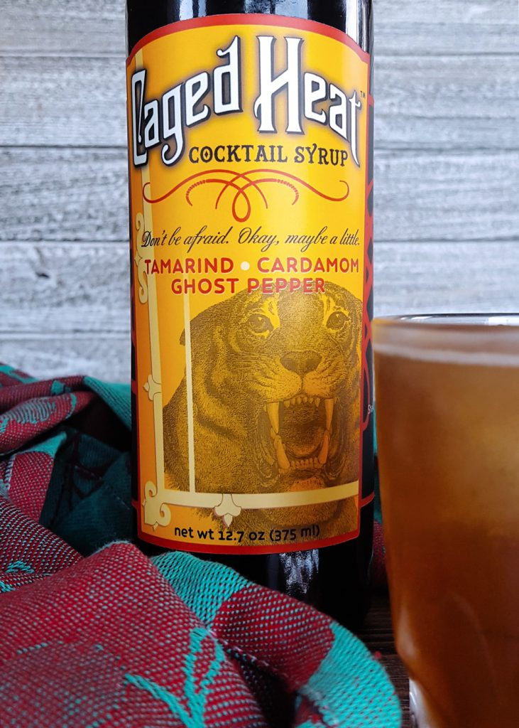 Close-up of a bottle of Caged Heat Cocktail Syrup with a cocktail in the foreground.