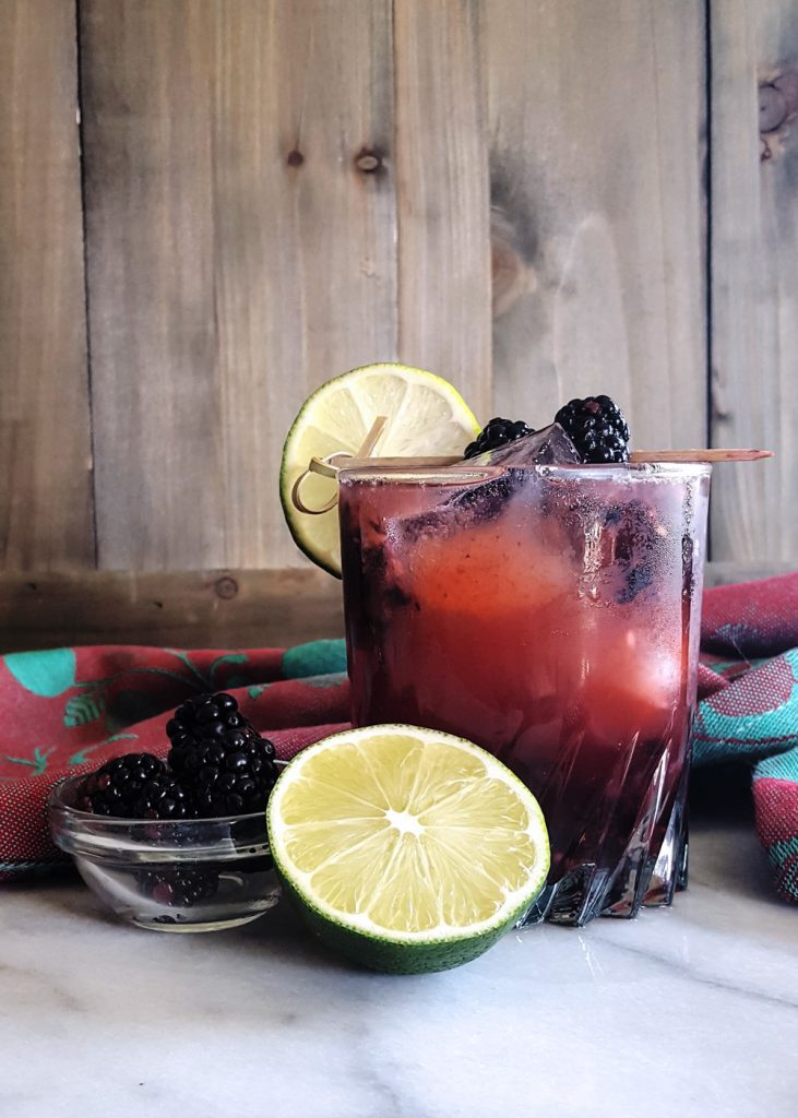 A Midsummer's Heat - A Spicy Blackberry Bourbon Smash Cocktail - garnished with a lime wheel and two blackberries.