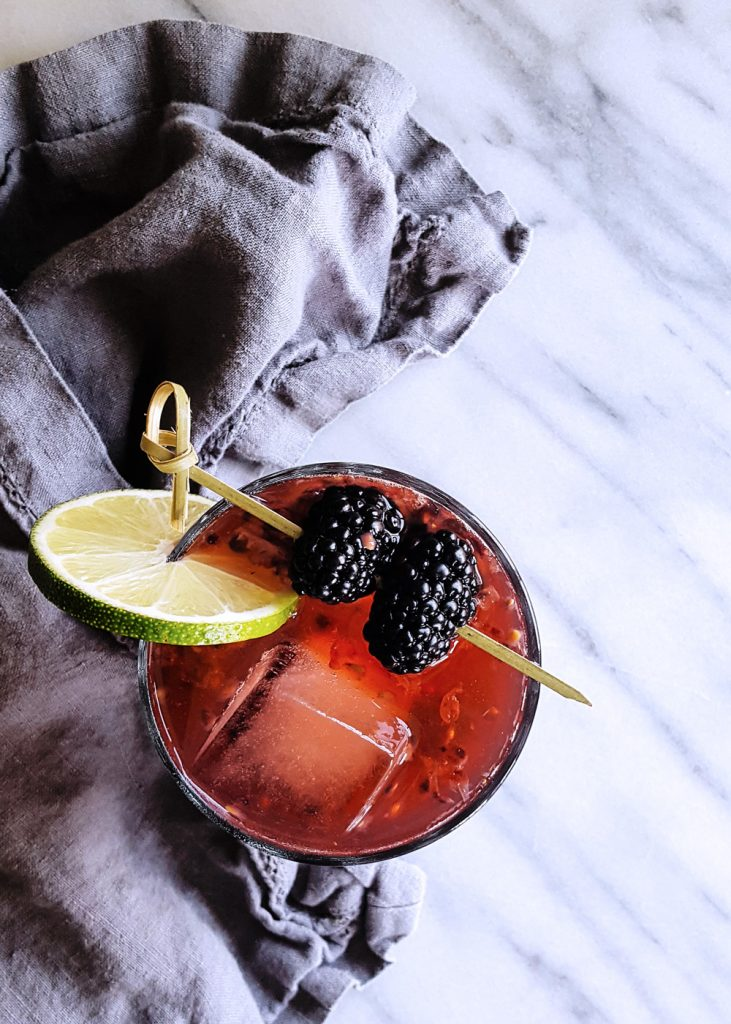 Top view of A Midsummer's Heat, garnished with two blackberries next to a grey linen napkin.
