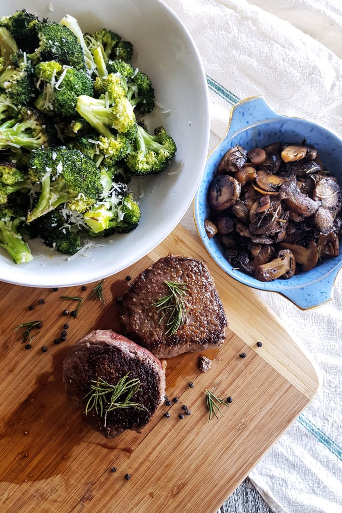 Two pan seared steak tenderloins, a bowl of wine glazed mushrooms, and a bowl of roasted broccoli. | FeastInThyme.com