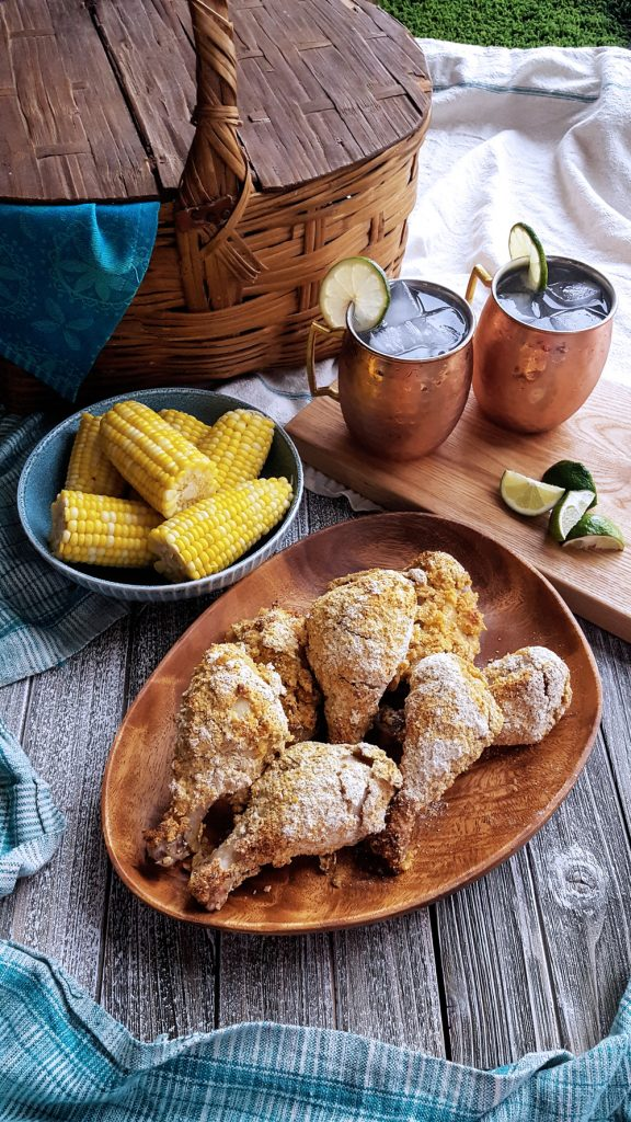 Full picnic spread of Cornmeal Crusted Picnic Chicken with basket, mugs, and corn on the cob.