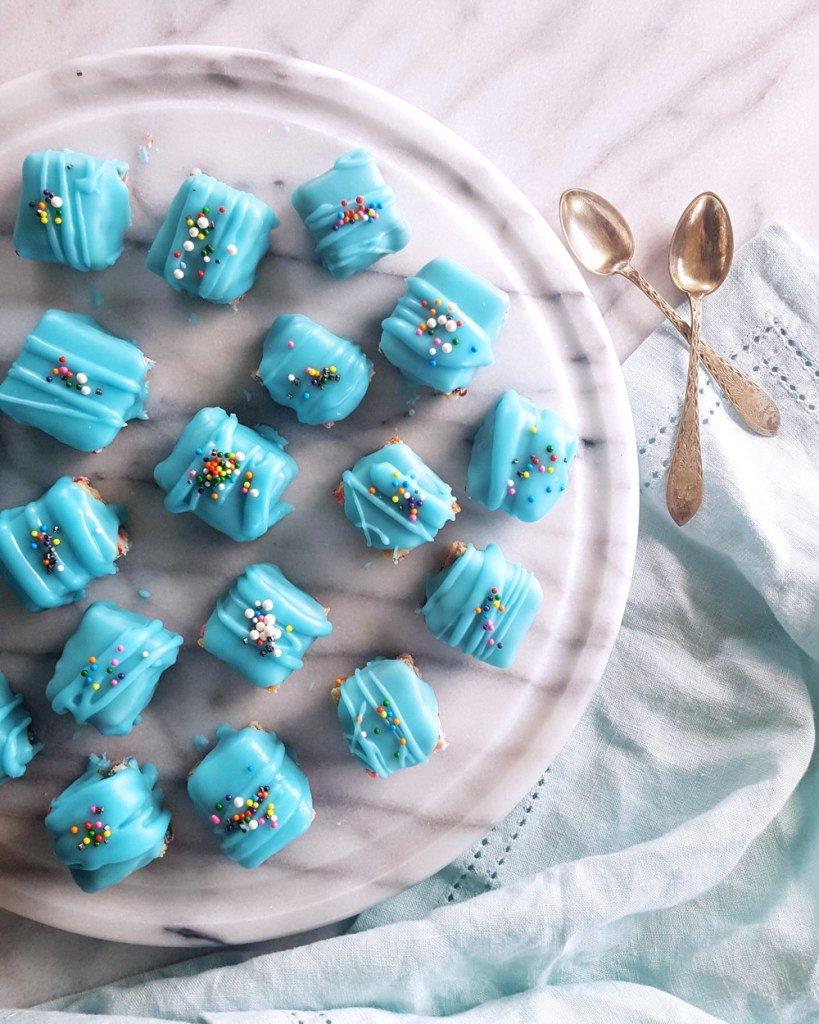 Funfetti Petit Fours arranged on a marble platter with two silver spoons. | FeastInThyme.com