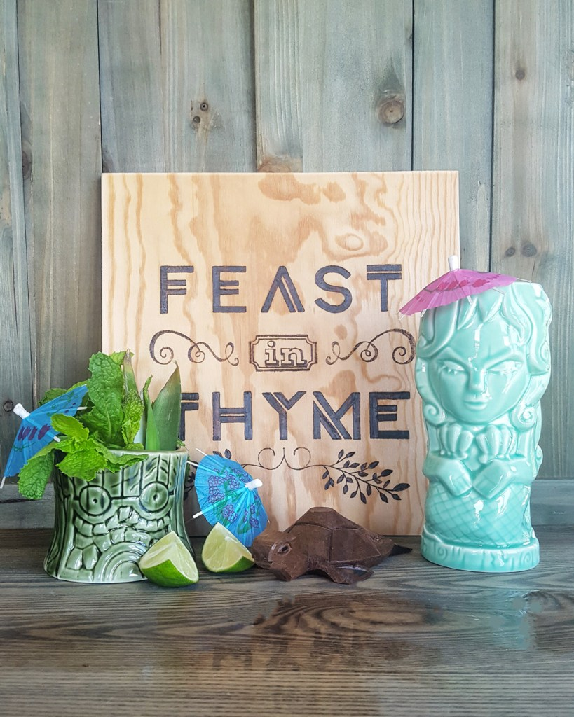 """Tiki mugs and garnishes around a sign that says """"Feast In Thyme"""""""
