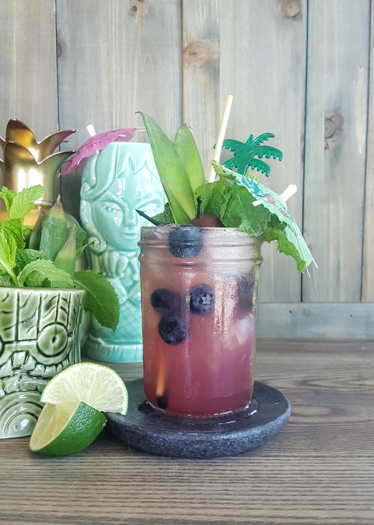 A blueberry rum tiki cocktail accompanied by mermaid and totem tiki mugs. | FeastInThyme.com