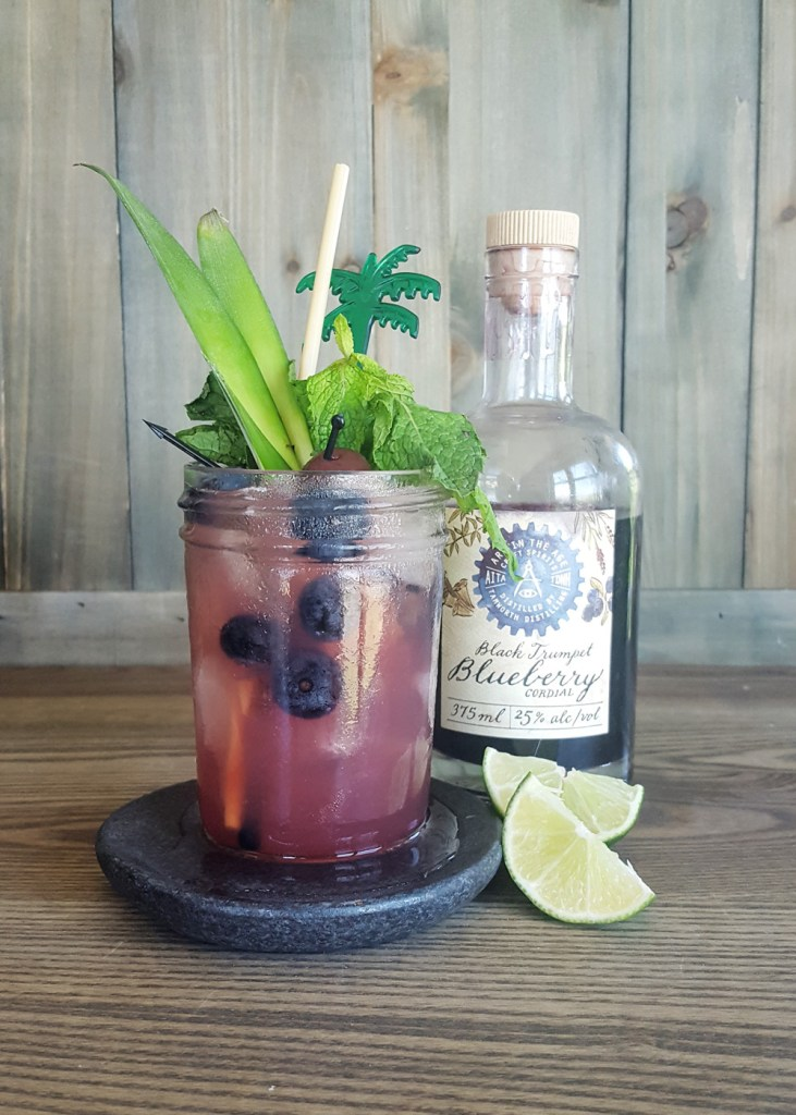 A blueberry rum tiki cocktail with a bottle of Black Trumpet Blueberry Cordial from @ArtInTheAge | FeastInThyme.com