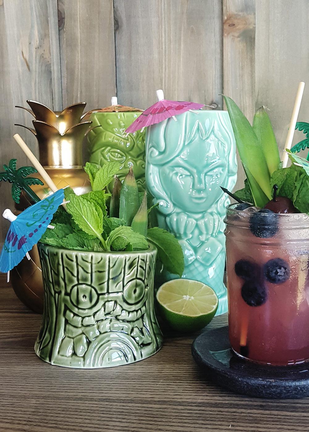 A selection of ceramic tiki mugs with a mason jar glass of purple tiki cocktail.