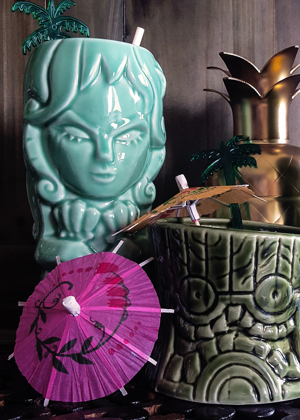 Ceramic tiki mugs in the shape of a mermaid and totem, with cocktail umbrellas.