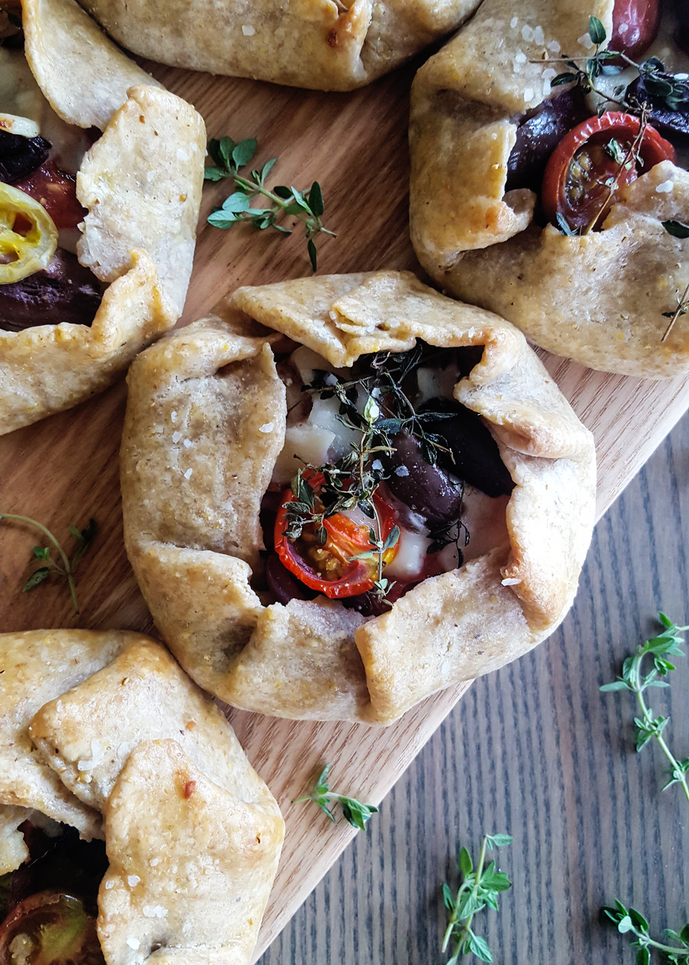 Close-up of a single Ratatouille Hand Pie on a platter with wooden plank background | FeastInThyme.com