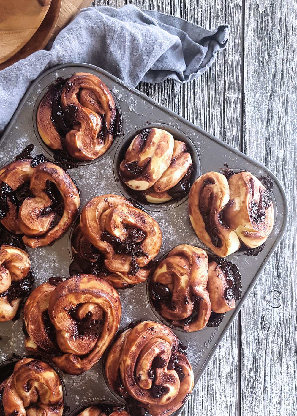 A tray of baked Cherry Chocolate Babka Pull Apart Muffins on a wooden background.