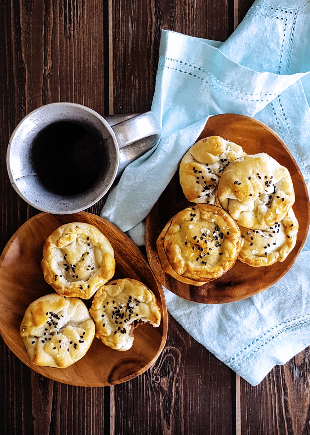 Two wooden plates of hand pies one a blue napkin with a pewter mug. | FeastInThyme.com
