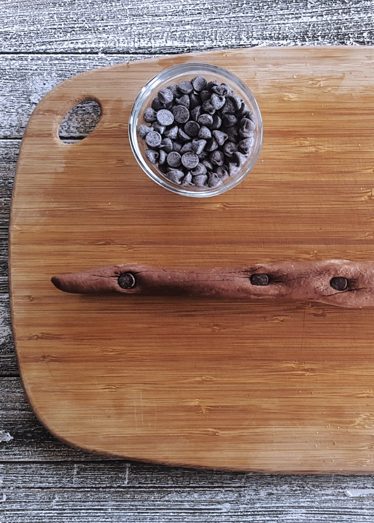 A rolled out rope of dough dotted with chocolate chips.