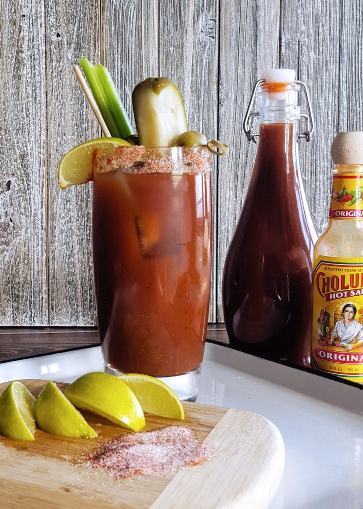 A tall glass of Spicy Bloody Mary Cocktail, with bottles of hot sauce and more Bloody Mary Mix behind.