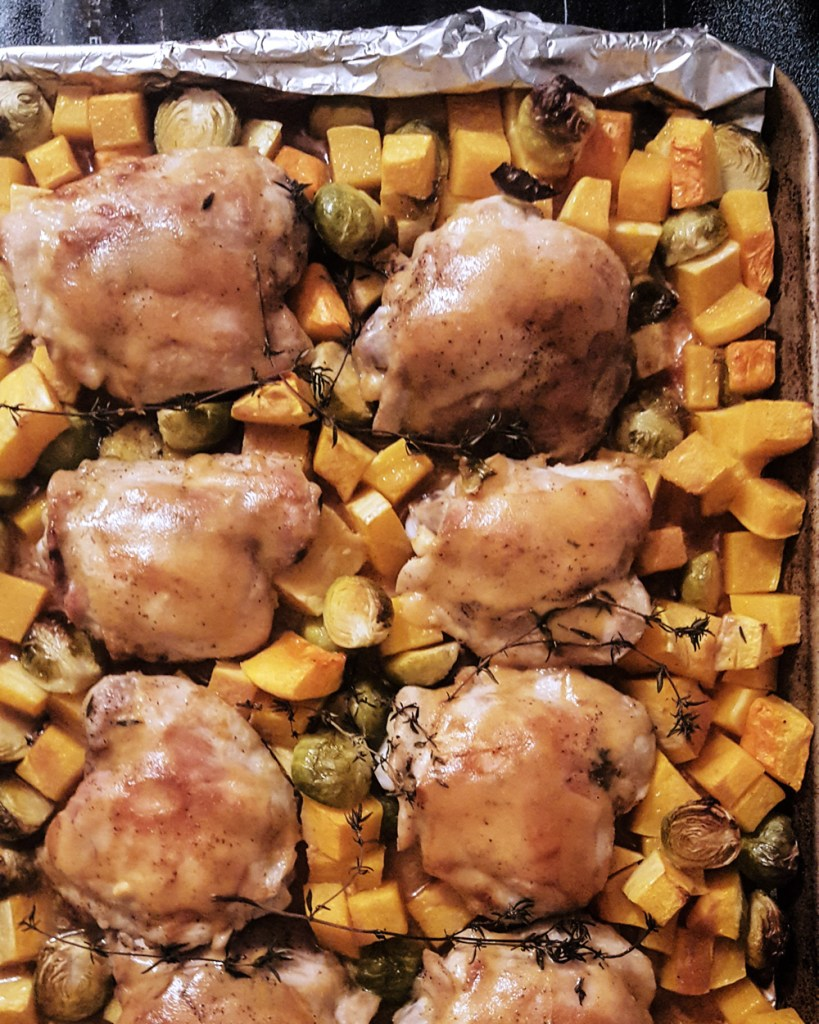 A sheet pan of roasted chicken, butternut squash, and brussel sprouts.