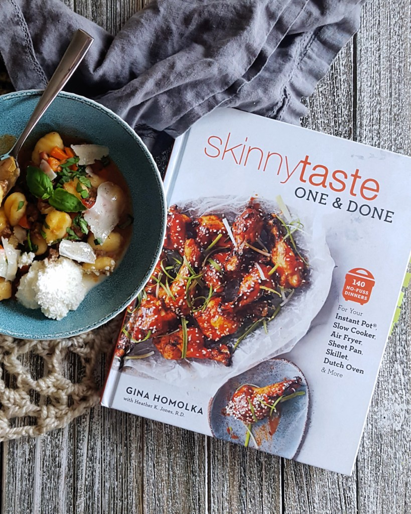 A copy of Skinnytaste One & Done next to a bowl of gnocchi.
