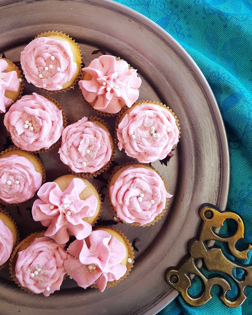 A silver plate of many tiny cupcakes frosted with pink icing like flowers on a blue clothe background.