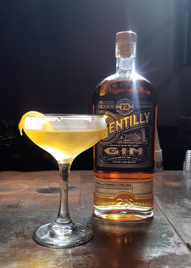A cocktail next to a bottle of barrel-aged Gentilly Gin.