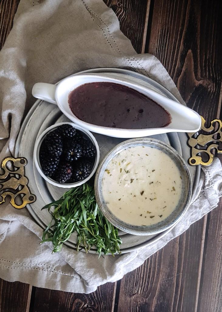 A platter of blackberry gravy, goat cheese sauce, whole blackberries, and fresh tarragon.