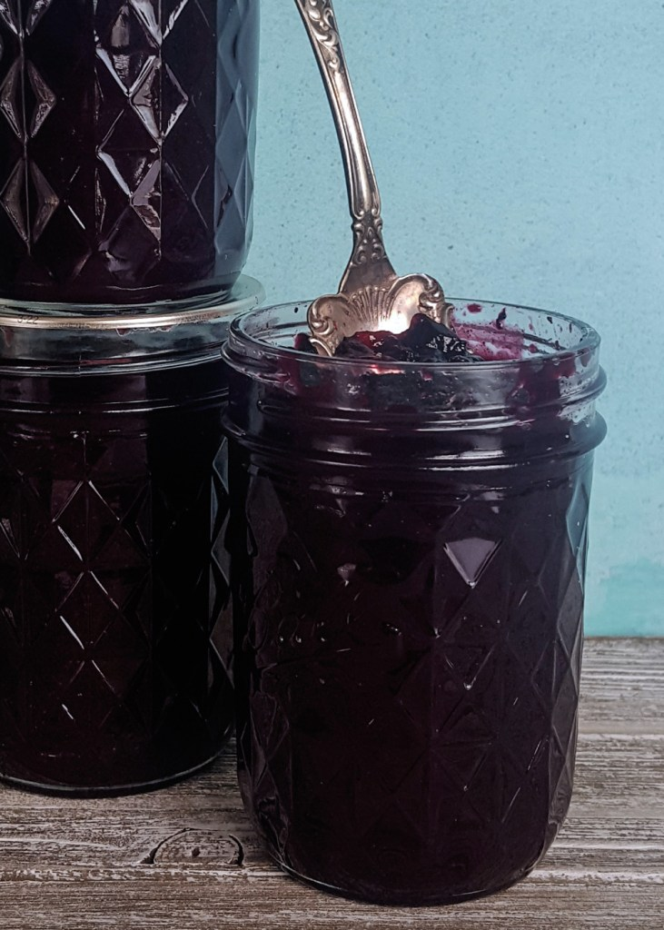 Three jars of spiced blueberry jam, one opened, with a blue background.
