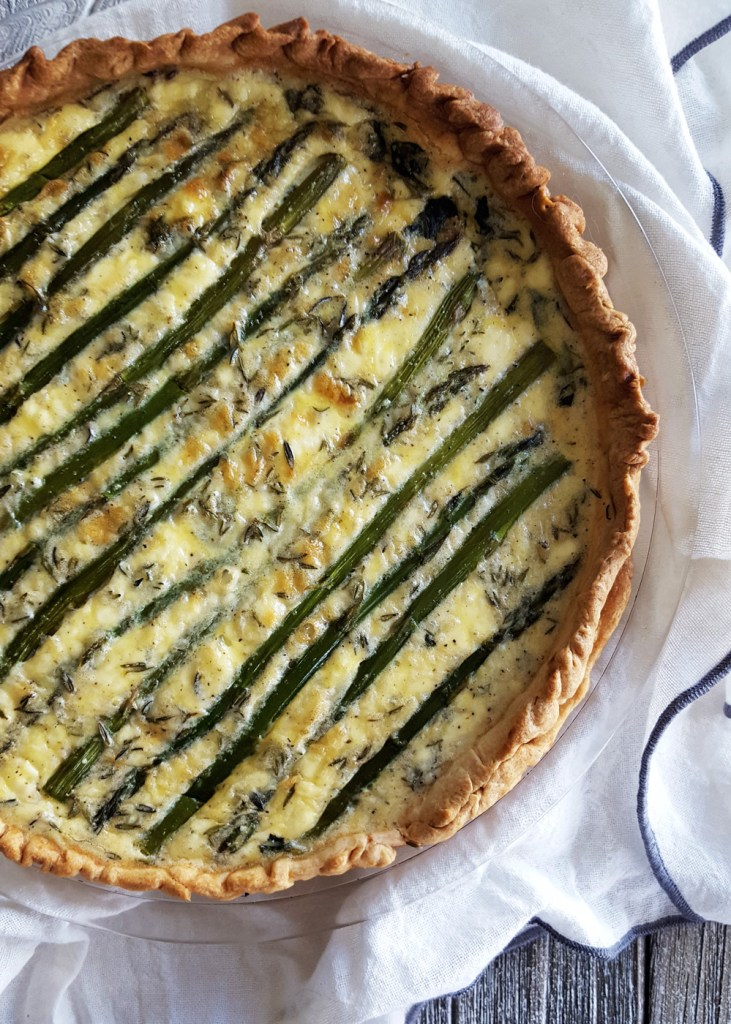 A large goat cheese quiche with asparagus carefully lined across the top on a white linen clothe.
