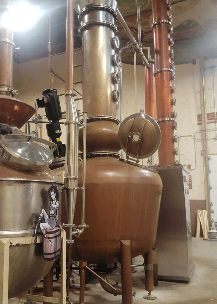 A side view of the copper stills in Painted Stave Distilling's production room.