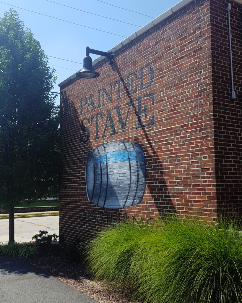 Outside facade featuring a large mural of the Painted Stave logo.
