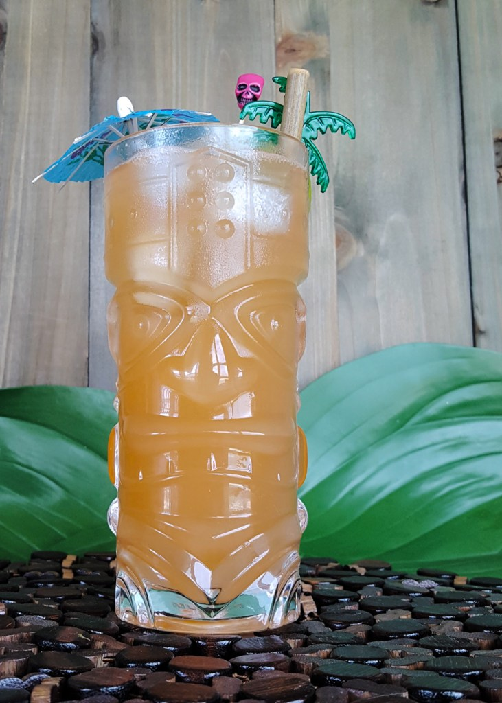 Imposing photo of a glass tiki mug filled with orange Zombie Punch.