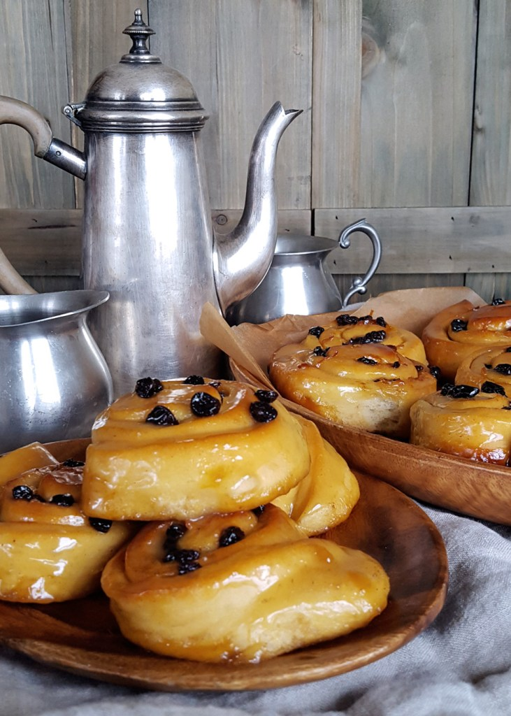 A shot of two platters of honey buns with a kettle behind.